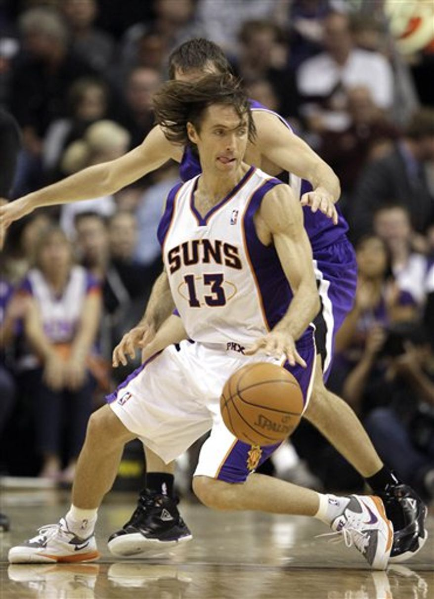 Phoenix Suns' Steve Nash (13) spins and dribble around Sacramento Kings' Beno Udrih, of Slovenia, during the second quarter of an NBA basketball game Friday, Nov. 12, 2010, in Phoenix. (AP Photo/Ross D. Franklin)