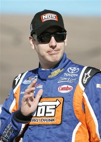 NASCAR Nationwide Series driver Kyle Busch waves to fans prior to qualifying for the Nationwide Series WYPALL 200 auto race at Phoenix International Raceway Saturday, Nov. 13, 2010, in Avondale, Ariz. (AP Photo/Jason Babyak)