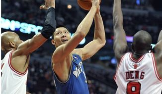Washington Wizards' Yi Jianlian drives between the Chicago Bulls' Taj Gibson left and Chicago Bulls' Luol Deng (9) during the first half of an NBA basketball game Saturday, Nov. 13, 2010, in Chicago. (AP Photo/Jim Prisching)