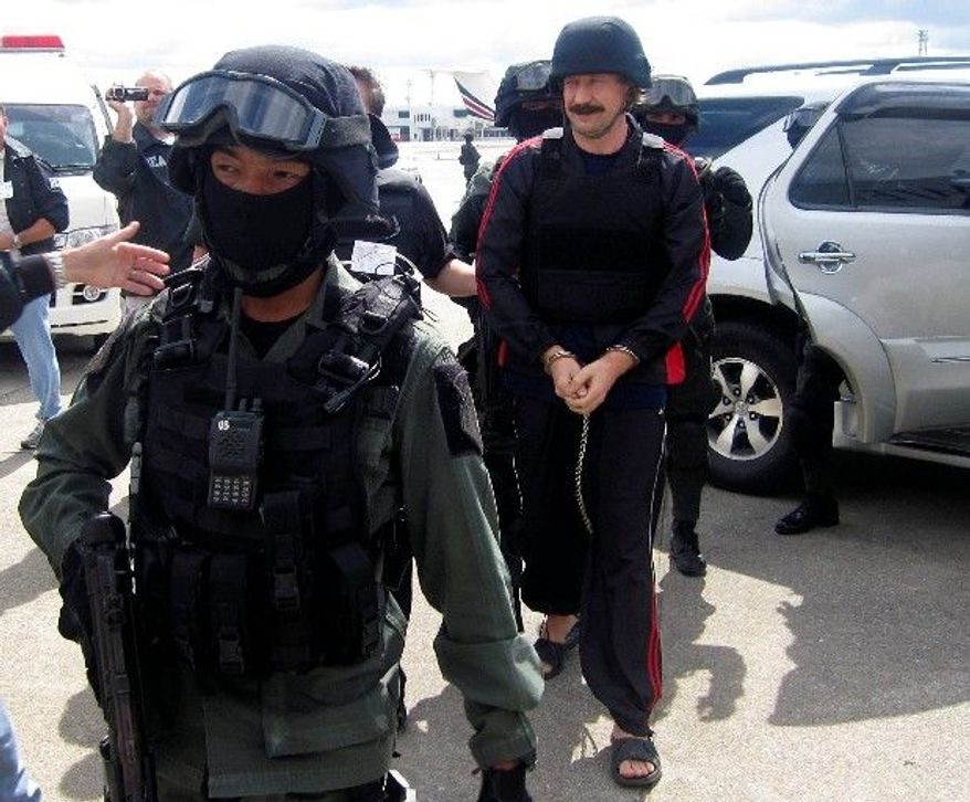 Associated Press Russian arms trafficker Viktor Bout, escorted by Thai police commandos, arrives at an airport in Bangkok on Tuesday. Thailand extradited Mr. Bout to the U.S. to face money laundering, wire fraud and other charges.