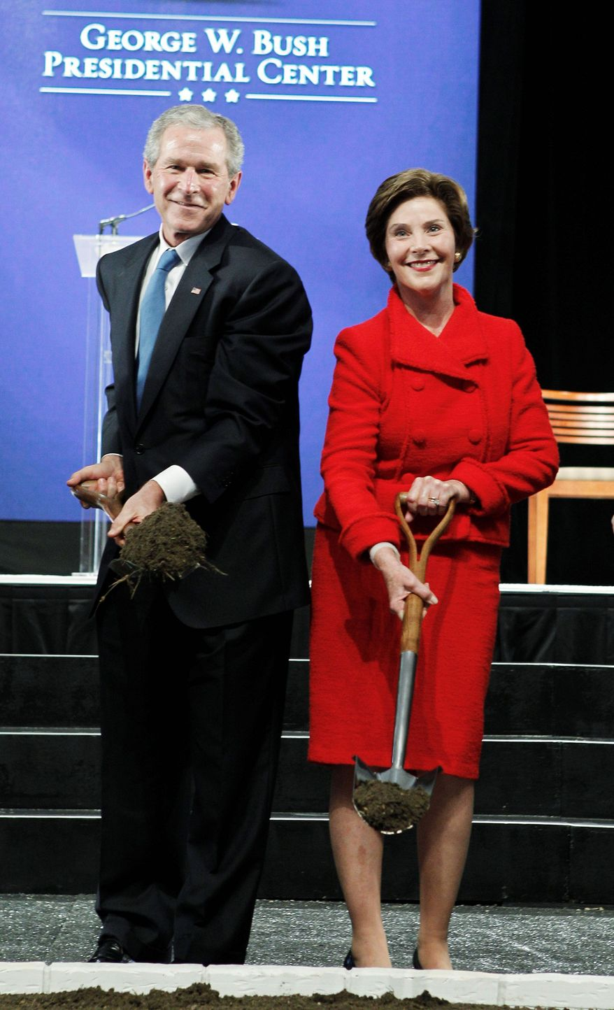 "ASSOCIATED PRESS PHOTOGRAPHS Former President George W. Bush and his wife, Laura, lift ceremonial shovels of dirt Tuesday in what he called ""the beginning of a journey"" for the George W. Bush Presidential Center."