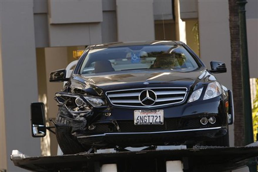 EDS: ADDS IDENTITY OF VICTIM -- A towtruck driver stands beside a damaged Mercedes E350 in which a woman, well-known Hollywood publicist Ronni Chasen, 64, was shot several times in the chest and killed on Tuesday, Nov 16, 2010 in Beverly Hills, Calif. A police statement says Chasen was shot several times at Sunset Boulevard and Whittier Drive. Her vehicle then crashed into a light pole. (AP Photo/Nick Ut)