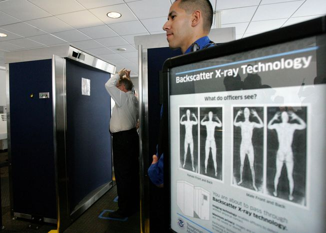 In this photo taken Sept. 1, 2010, Transportation Security Administration employee Anthony Brock, left, demonstrates a new full-body scanner at San Diego's Lindbergh Field, with TSA employee Andres Lozano in San Diego.  (AP Photo/San Diego Union Tribune, Eduardo Contreras)