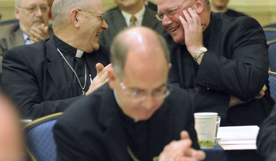 Bishop Kevin Vann, left, of Fort Worth, Texas, congratulates Archbishop Timothy Dolan, right, of New York after Archbishop Dolan was elected president of the U.S. Conference of Catholic Bishops during the conference's annual fall meeting Tuesday, Nov. 16, 2010, in Baltimore. (AP Photo/Steve Ruark)