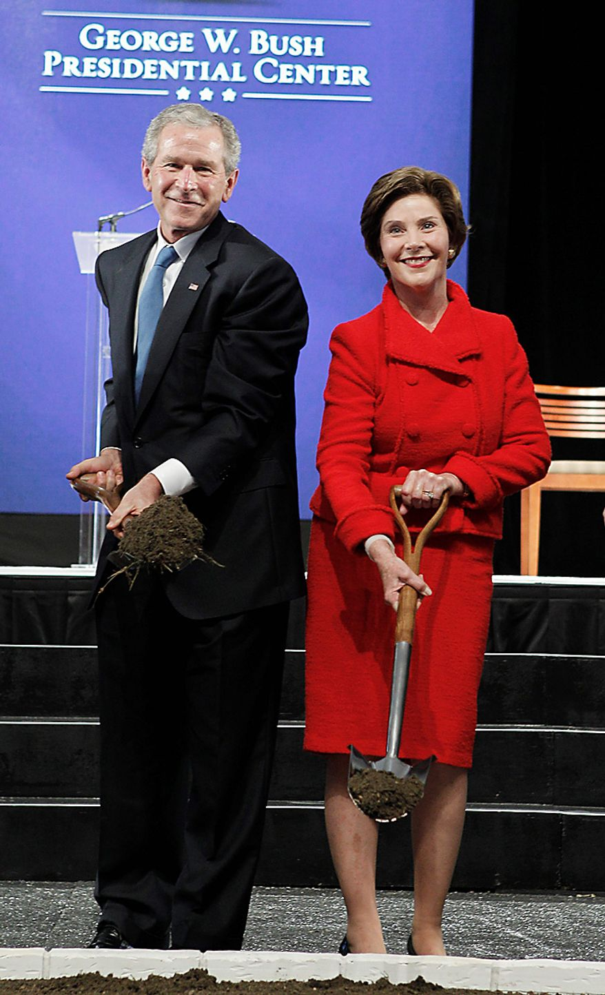 Former President George W. Bush, left,, and his wife Laura Bush pick up shovels of dirt during the ground breaking ceremony for the President George W. Bush Presidential Center at SMU in Dallas, Tuesday, Nov. 16, 2010. (AP Photo/LM Otero)