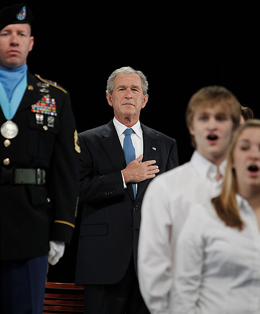 Former President George W. Bush, center, places his hand on his chest during the national anthem before the ground breaking ceremony for the President George W. Bush Presidential Center at SMU in Dallas, Tuesday, Nov. 16, 2010. (AP Photo/LM Otero)