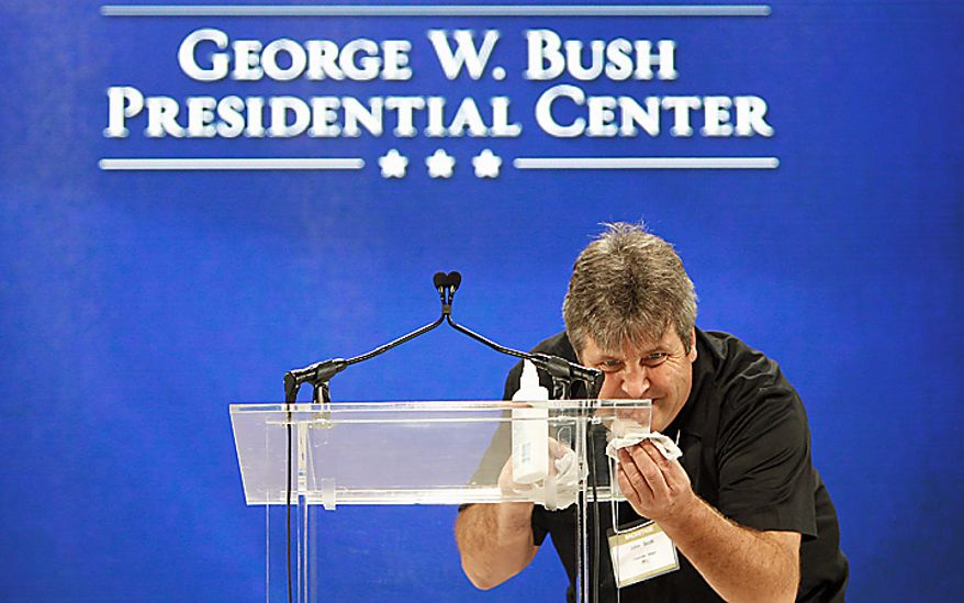John Scott cleans the podium on the stage in preparation for the groundbreaking ceremony for the George W. Bush Presidential Center in Dallas, Tuesday, Nov. 16, 2010. (AP Photo/LM Otero)
