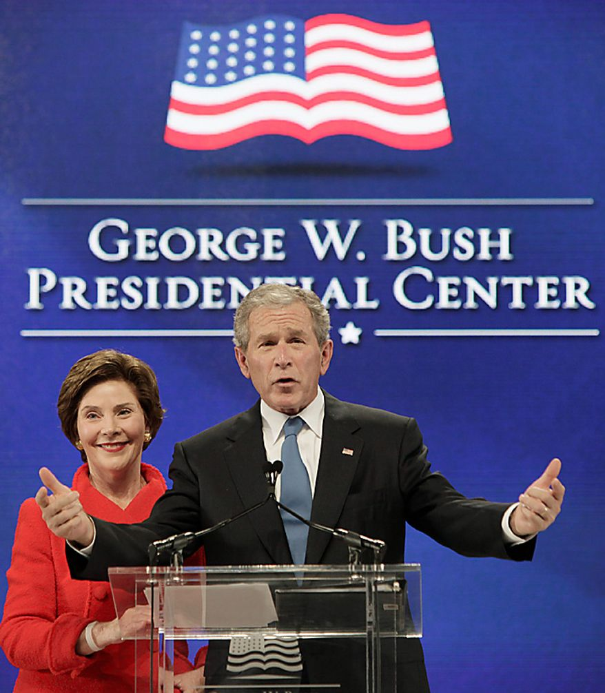 Former President George W. Bush, right, speakes with his wife Laura Bush by his side during the ground breaking ceremony for the President George W. Bush Presidential Center at SMU in Dallas, Tuesday, Nov. 16, 2010. (AP Photo/LM Otero)
