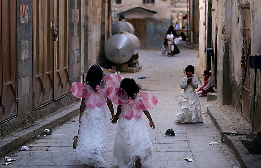 Two Yemeni sisters dressed as angels, hold hands while walking in an alley of the old city, on the first day of the Muslim holiday of Eid al-Adha, or Feast of the Sacrifice, in Sanaa, Yemen, Tuesday, Nov. 16, 2010.(AP Photo/Muhammed Muheisen)