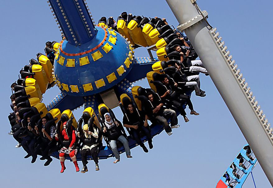 Iraqis enjoy a ride at Amusement City in Baghdad, Iraq, Tuesday, Nov. 16, 2010 at the start of the Islamic festival Eid al-Adha, or Feast of Sacrifice. (AP Photo/Karim Kadim)