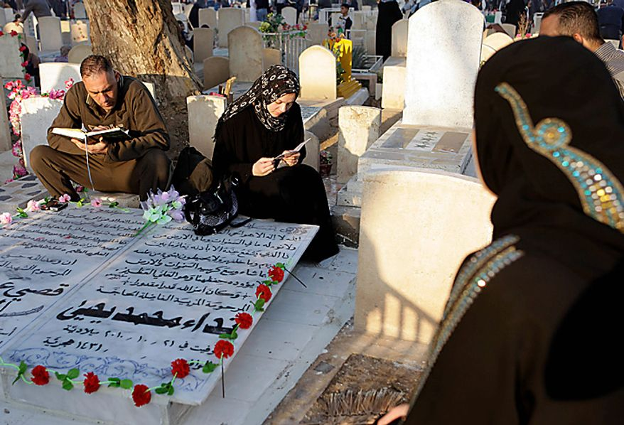 Iraqi Sunni Muslims pray over the grave of a relative at a cemetery on the first day of Eid al-Adha in Baghdad, Iraq, Tuesday, Nov. 16, 2010. Muslims around the world gathered on Tuesday to celebrate Eid al-Adha, or the Feast of Sacrifice.(AP Photo/Karim Kadim)