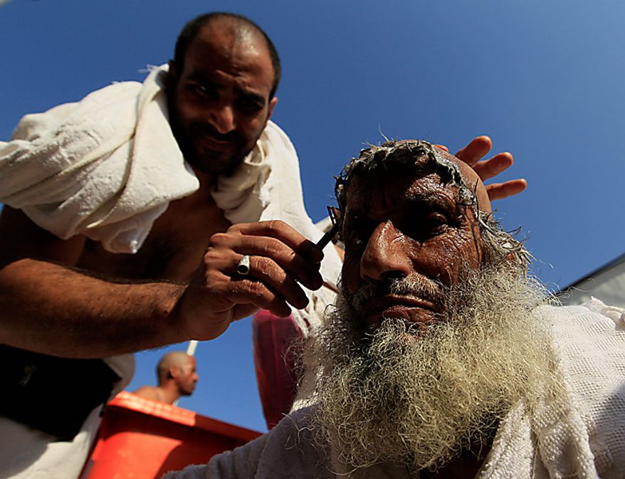 A Muslim pilgrim has his head shaved, after throwing pebbles at a stone pillar representing the devil, during the Hajj pilgrim in Mina near Mecca, Saudi Arabia, Tuesday, Nov. 16, 2010. The last stage of the annual Hajj pilgrimage, the symbolic stoning of the devil, began on Friday. The first day of stoning also marks the start of the Islamic holiday of Eid al-Adha, or feast of sacrifice, when Muslims around the world slaughter sheep and cattle in remembrance of Abraham's near-sacrifice of his son. (AP Photo/Hassan Ammar)