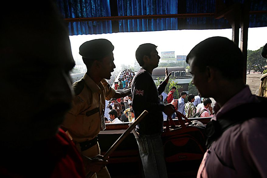 A Bangladesh railway policeman tries to reprimand a man from jumping from a foot over bridge to the rooftop of an overcrowded train as scores of people try to reach home to celebrate Eid al-Adha at the Airport train station, outskirts of Dhaka, Bangladesh, Tuesday, Nov. 16, 2010. (AP Photo/Pavel Rahman)