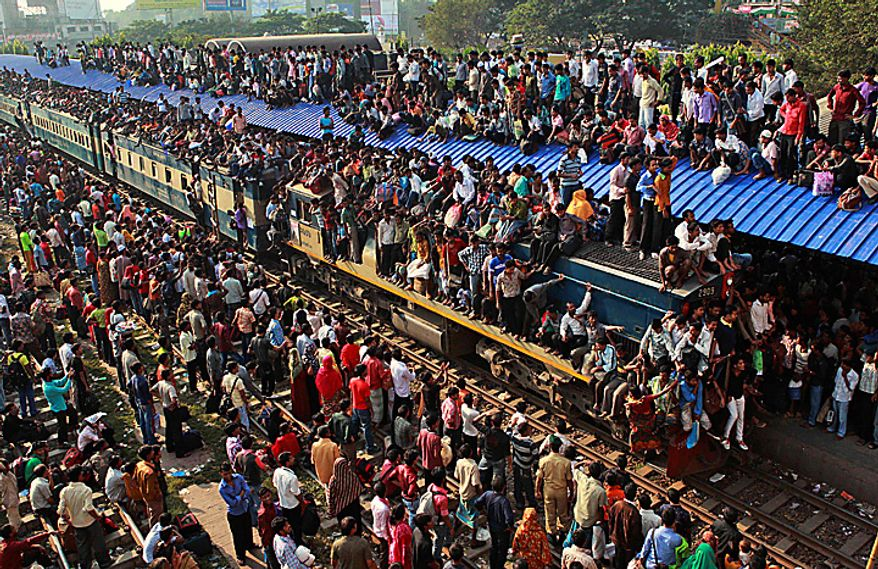 Bangladeshi passengers sit on the roof and sides of an overcrowded train as others wait on the roof of a platform as they try to reach their homes to celebrate Eid al-Adha at the Airport train station, outskirts of Dhaka, Bangladesh, Tuesday, Nov. 16, 2010. (AP Photo/Pavel Rahman)