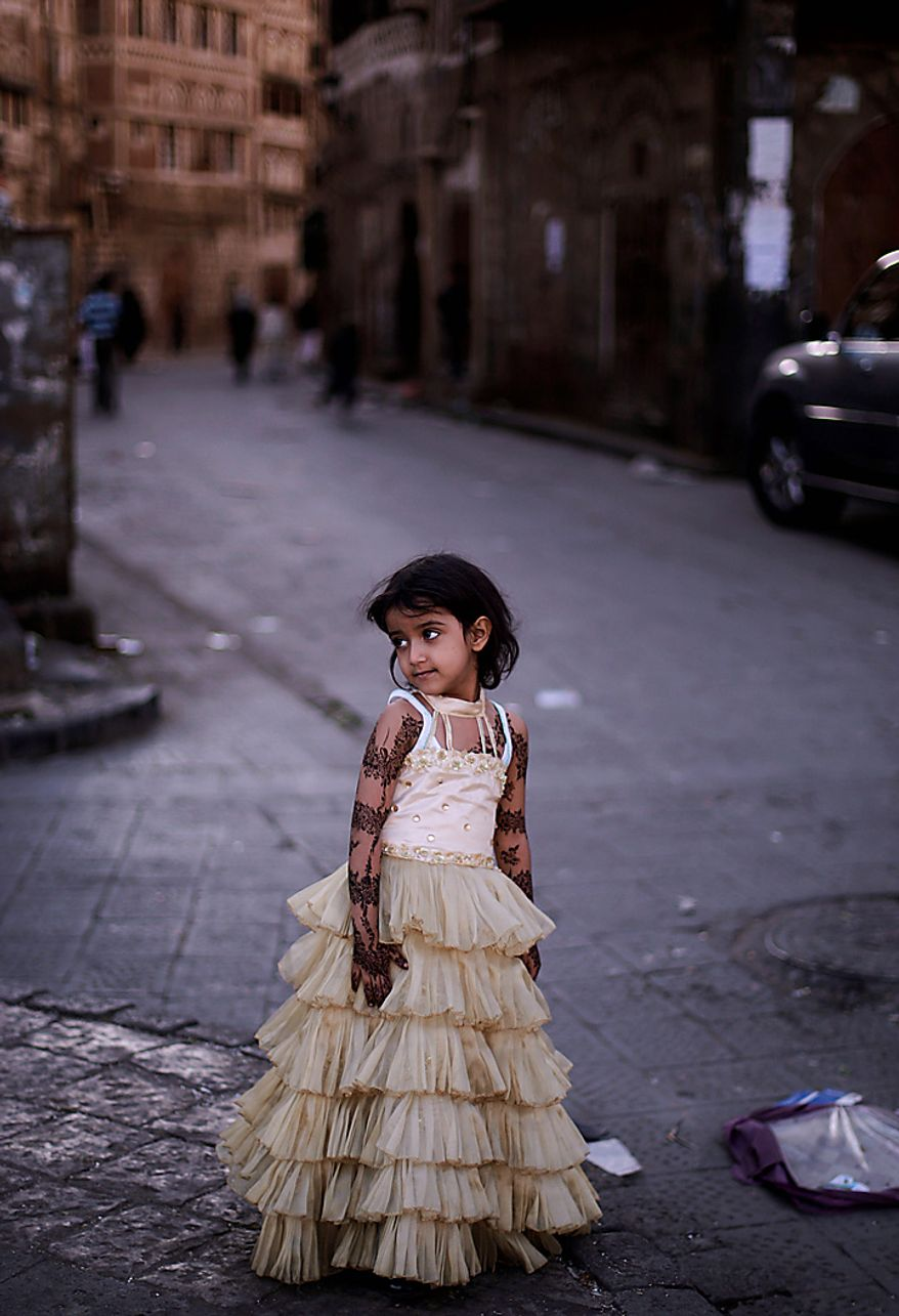 A Yemeni girl wearing a new dress as she stands  in an alley of the old city, on the first day of the Muslim holiday of Eid al-Adha, or Feast of the Sacrifice, in Sanaa, Yemen, Tuesday, Nov. 16, 2010. (AP Photo/Muhammed Muheisen)