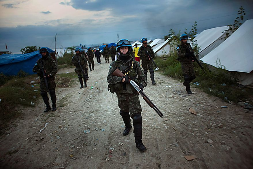 UN peacekeepers from Brazil patrols at a earthquake survivors refugee camp in the outskirts of Port-au-Prince, Haiti, Monday Nov. 15, 2010. Protesters who hold Nepalese U.N. peacekeepers responsible for an outbreak of cholera that has killed 1,000 in three weeks threw stones and threatened to set fire to a base in Cap-Haitien, the country's second-largest city Monday, Haitian radio and eyewitnesses reported.(AP Photo/Emilio Morenatti)
