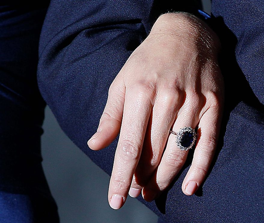 Britain's Prince William and his fiancee Kate Middleton, wearing the engagement of Princess Diana,  pose for the media at St. James's Palace in London, Tuesday Nov. 16, 2010, after they announced their engagement. The couple are to wed in 2011. (AP Photo/Kirsty Wigglesworth)