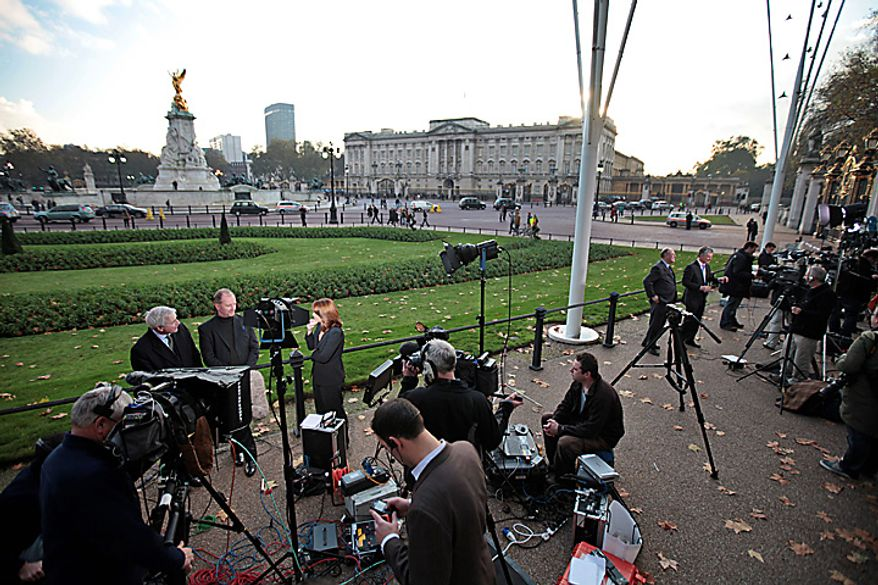 Members of the media work on the story of Britain's Prince William engagement, across the street from Buckingham Palace, background, in central London, Tuesday, Nov. 16, 2010. Britain's Prince William, who is second in line to the throne, and girlfriend Kate Middleton are engaged and will marry next spring or summer in London _ a royal wedding that Britons have been eagerly awaiting for years. The announcement Tuesday by royal officials ends an on-again, off-again romance that began after the two met more than eight years ago as students at the University of St. Andrews in Scotland. Prince William turned 28 in June and recently completed training a Royal Air Force search and rescue pilot.(AP Photo/Lefteris Pitarakis)