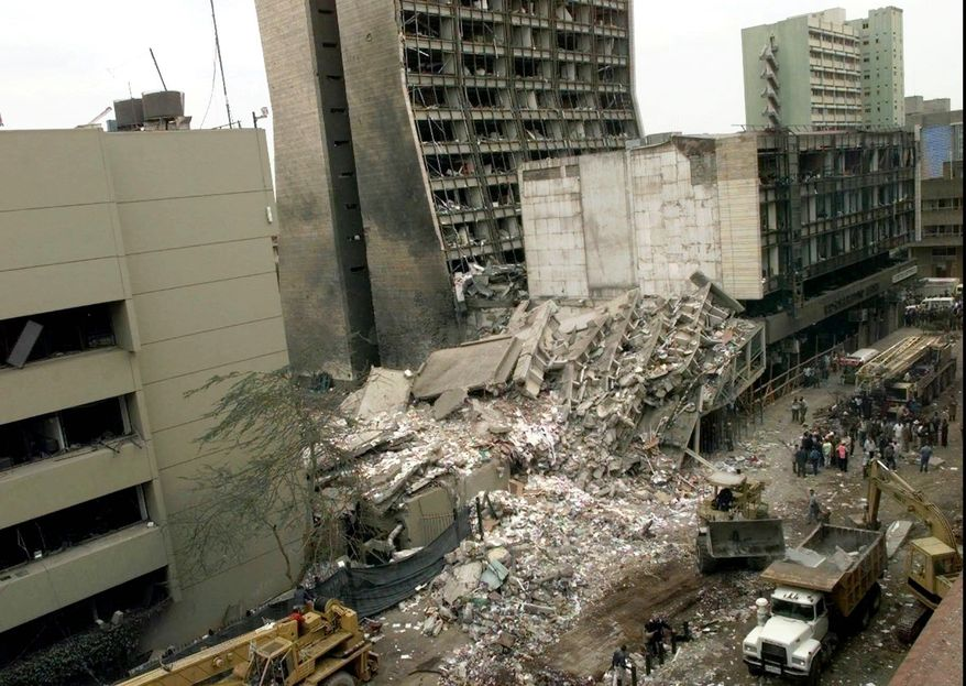 The United States Embassy, left, is pictured with blasted ruins next to it in downtown Nairobi, Kenya Saturday, Aug. 8, 1998 the day after terrorist bombs in Kenya and Dar es Salaam, Tanzania exploded killing at least 130 and injuring at least 2,200. Officials in the United States, Kenya and Tanzania refused to speculate on who was responsible. (AP Photo/Dave Caulkin)