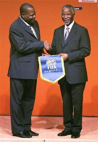 FILE - The Oct. 24, 2006 file photo shows then South African President Thabo Mbeki, right, being presented with a FIFA pennant by FIFA Executive Committee member, Dr. Amos Adamu, at the opening of a  2010 soccer World Cup Kick Off Workshop in Cape Town. FIFA suspended executive committee members Amos Adamu and Reynald Temarii from the 2018 and 2022 World Cup hosting vote on Thursday Nov. 18. 2010 after completing a corruption investigation, and cleared bidders Qatar and Spain-Portugal of collusion. (AP Photo/Obed Zilwa, File)