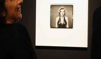 """A visitor watches a 1957 photograph called """"Marilyn Monroe, actress""""  by late U.S photographer Richard Avedon at Christie's auction house in Paris, Thursday Nov.18, 2010. More than 60 photographs for the Avedon Foundation will be auctioned next Saturday.  (AP Photo/Jacques Brinon)"""