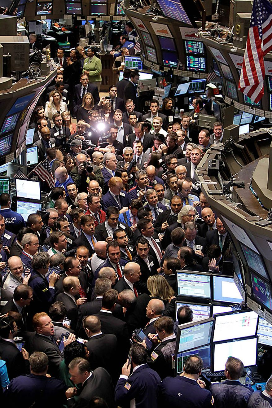Traders gather near the post where General Motors Co. stock trades at the New York Stock Exchange, Thursday, Nov. 18, 2010.  (AP Photo/Seth Wenig)