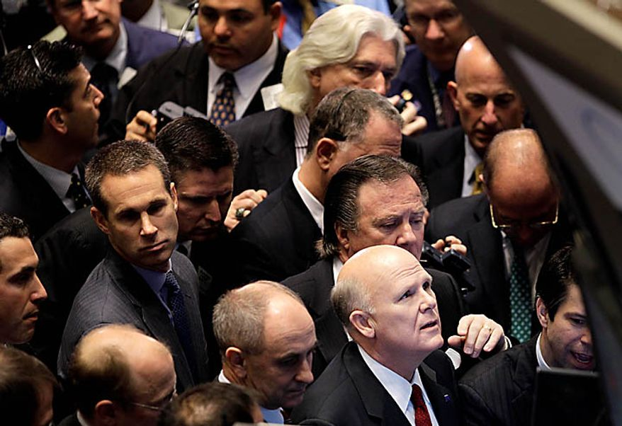 General Motors CEO Dan Akerson, bottom right, stands among traders at the post where GM stock is traded at the New York Stock Exchange in New York, Thursday, Nov. 18, 2010.  (AP Photo/Seth Wenig)