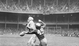 "FILE - This Nov. 9, 1946, file photo shows Army fullback Felix ""Doc"" Blanchard (35), center left in front of the official, fumbling the ball, in air at center, during the first half against Notre Dame, at Yankee Stadium in New York. Teammate Glen Davis (41), left foreground, recovered the ball. Identifiable Notre Dame players are  Bill Fischer (72) and Jim Martin (38). Back then, Notre Dame and Army were at the top of the sport. Their rivalry was THE rivalry. College football was still a regional game, but the Fighting Irish and Black Knights had national followings. (AP Photo/File)"