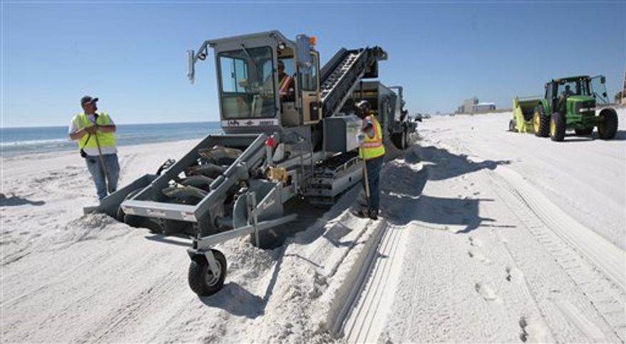 In this photo taken Tuesday, Nov. 9, 2010, BP operates a deep sand cleaning operation in Orange Beach, Ala. The oil company has launched its biggest push yet to deep-clean the tourist beaches that were coated with crude during the worst of the Gulf oil spill. Machines are digging down into the sand to remove buried tar mats left from the Deepwater Horizon disaster. (AP Photo/Dave Martin)