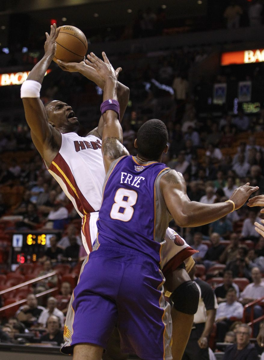 Miami Heat forward Chris Bosh, left, shoots as he is fouled by Phoenix Suns center Channing Frye (8) in the first quarter during an NBA basketball game in Miami on Wednesday, Nov. 17, 2010. (AP Photo/Lynne Sladky)