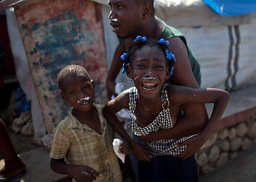 earthquake refugees react after receiving tear gas during a protest in Port-au-Prince, Haiti, Thursday, Nov. 18, 2010. Following days of rioting in northern Haiti over suspicions that U.N. soldiers introduced a cholera epidemic that has killed more than 1,000 people, protesters in Haiti's capital clashed with police Thursday lashing out at U.N. peacekeepers and the government, blocking roads and attacking foreigners' vehicles. (AP Photo/Ramon Espinosa)