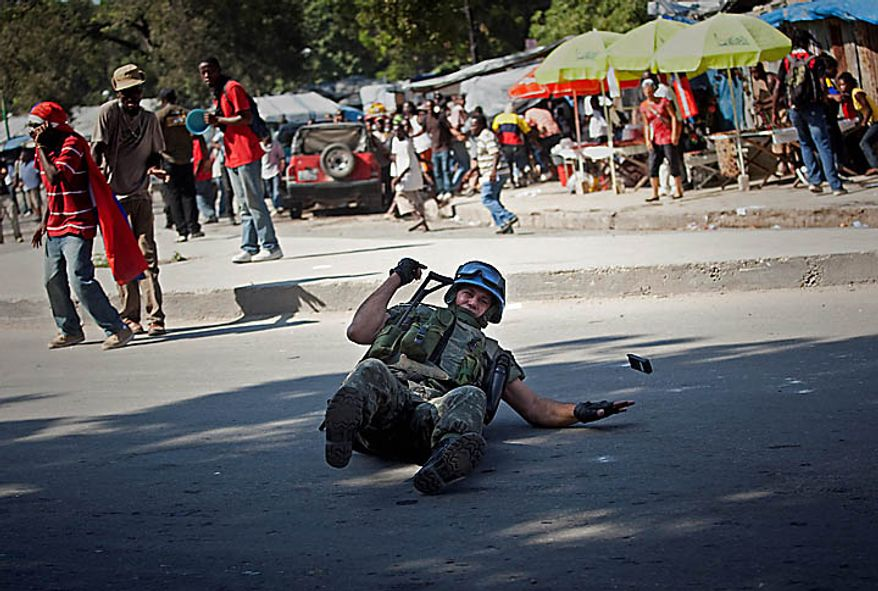 An UN peacekeepers from Brazil falls from his vehicle next to demonstrators during a protest in Port-au-Prince, Haiti, Thursday, Nov. 18, 2010. Following days of rioting in northern Haiti over suspicions that U.N. soldiers introduced a cholera epidemic that has killed more than 1,000 people, protesters in Haiti's capital clashed with police Thursday lashing out at U.N. peacekeepers and the government, blocking roads and attacking foreigners' vehicles (AP Photo/Emilio Morenatti)