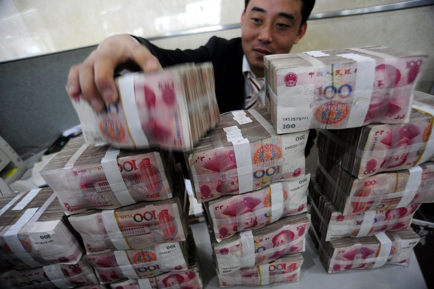 In this file photo taken on Nov. 17, 2009, a bank clerk stacks up renminbi banknotes at a bank in Hefei in central China's Anhui province. China on Friday, Nov. 19, 2010, criticized a U.S. congressional report that called on Washington to do more to force Beijing to increase the value of its currency. (AP Photo)