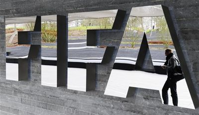 ** FILE ** A man passes by the FIFA logo prior to a press conference following a meeting of the Executive Committee on Friday, Nov. 19, 2010, in Zurich, Switzerland. (AP Photo/Keystone/Steffen Schmidt)