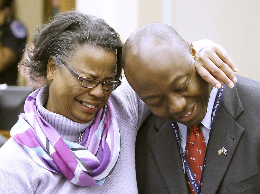 Rep.-elect Tim Scott, R-S.C., right, is hugged by his mother Frances Scott, on Capitol Hill in Washington, Friday, Nov. 19, 2010, after she drew number 44, her son's high school football number,  for her son as the incoming House of Representatives members drew in a lottery to pick their office space. (AP Photo/Harry Hamburg)