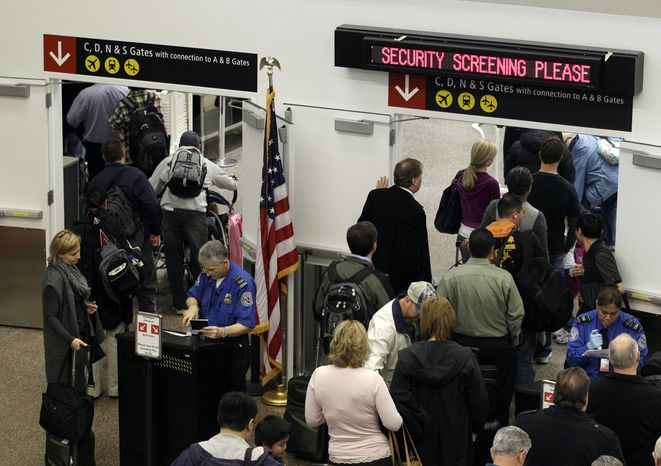 ** FILE ** TSA agents check passenger identification at a security gate on Friday, Nov. 19, 2010, at Seattle-Tacoma International Airport in Seattle. (AP Photo/Ted S. Warren)
