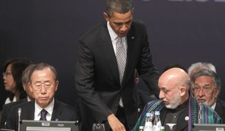 U.S. President Barack Obama, center, walks over to greet Afghanistan President Hamid Karzai, right, seated, during the start of the Afghanistan Opening Session at NATO Summit in Lisbon, Portugal, on Saturday, Nov. 20, 2010. Also, sitting at left is United Nations Secretary-General, Ban Ki-moon. (AP Photo/Pablo Martinez Monsivais)