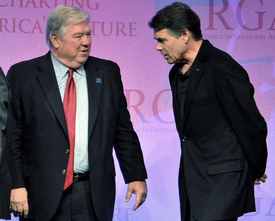ASSOCIATED PRESS Mississippi Gov. Haley Barbour (left) and Texas Gov. Rick Perry share a moment on stage at the Republican Governors Association meeting Wednesday in San Diego. Mr. Barbour is the outgoing chairman of the association and Mr. Perry is the incoming chairman.