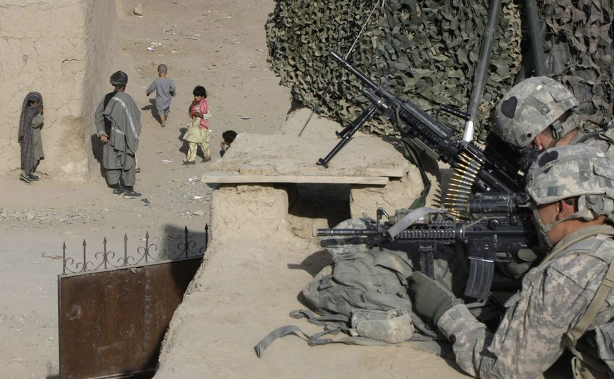 U.S. soldiers from First Battalion, 502nd Infantry Regiment, 101st Airborne Division set their positions Sunday in West Now Ruzi village, in Panjwai district, Afghanistan. (Associated Press)