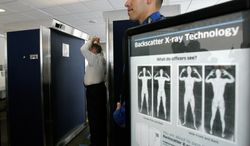 """**FILE** Transportation Security Administration employee Anthony Brock (left) demonstrates a new full-body scanner with TSA employee Andres Lozano at San Diego's Lindbergh Field on Sept. 1, 2010. The American Civil Liberties Union has denounced the machines as a """"virtual strip search."""" (Associated Press/San Diego Union Tribune)"""