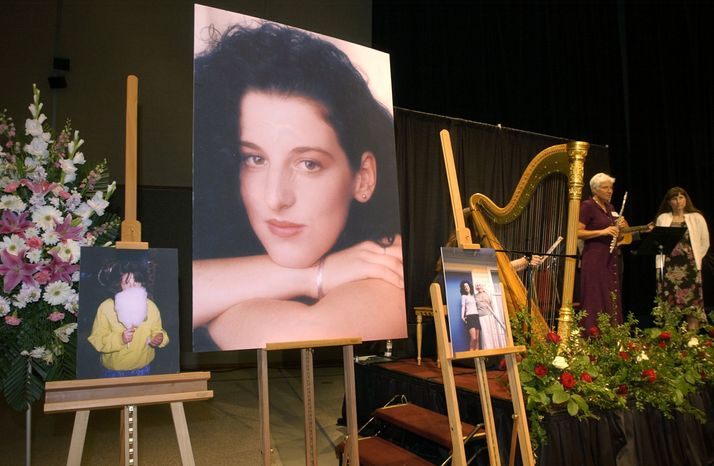 In this May 28, 2002, file photo taken at the Modesto Centre Plaza in Modesto, Calif. photos of Chandra Levy are on display as musicians, right, stand by at the memorial service for Levy. Jurors in Washington on Monday, Nov. 22, 2010, convicted Ingmar Guandique of her murder. (AP Photo/Debbie Noda, Pool, File)