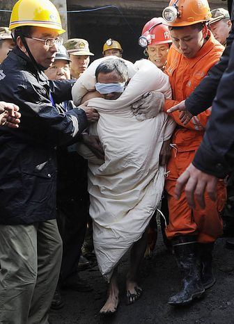 In this photo released by China's Xinhua News Agency, miner Liu Hengqiang, center, is rescued at the Batian coal mine in Xiaohe Town of Weiyuan County, southwest China's Sichuan Province, Monday, Nov. 22, 2010. Barefoot and wrapped in white quilts, 29 miners were pulled out of a Chinese coal mine Monday after being trapped by a flood and waiting a day for rescuers to pump out water. (AP Photo/Xinhua, Jiang Hongjing)