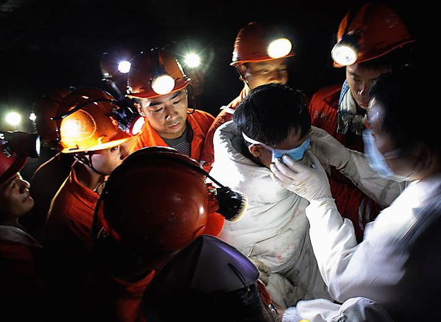 A medical worker adjusts an eye cover on a trapped miner before moving him out from the flooded Batian Coal Mine in Xiaohe town of Weiyuan county in southwest China's Sichuan province Monday, Nov. 22, 2010. Emergency crews drained the flooded Chinese coal mine and rescued all 29 trapped workers Monday, ending a daylong rescue drama. (AP Photo/Color China Photo)