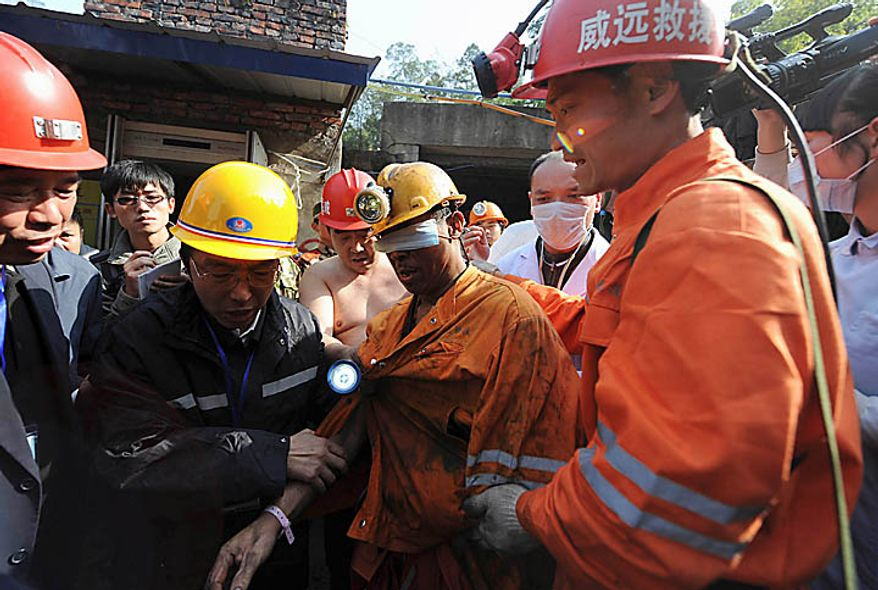 In this photo released by China's Xinhua News Agency, Liu Mingquan, center, the first miner rescued among the 29 miners trapped underground, gets help from rescue workers at the Batian coal mine in Xiaohe Town of Weiyuan County, southwest China's Sichuan Province, Monday, Nov. 22, 2010. Emergency crews drained a flooded Chinese coal mine and rescued all 29 trapped workers Monday, ending a daylong rescue drama. (AP Photo/Xinhua, Jiang Hongjing)