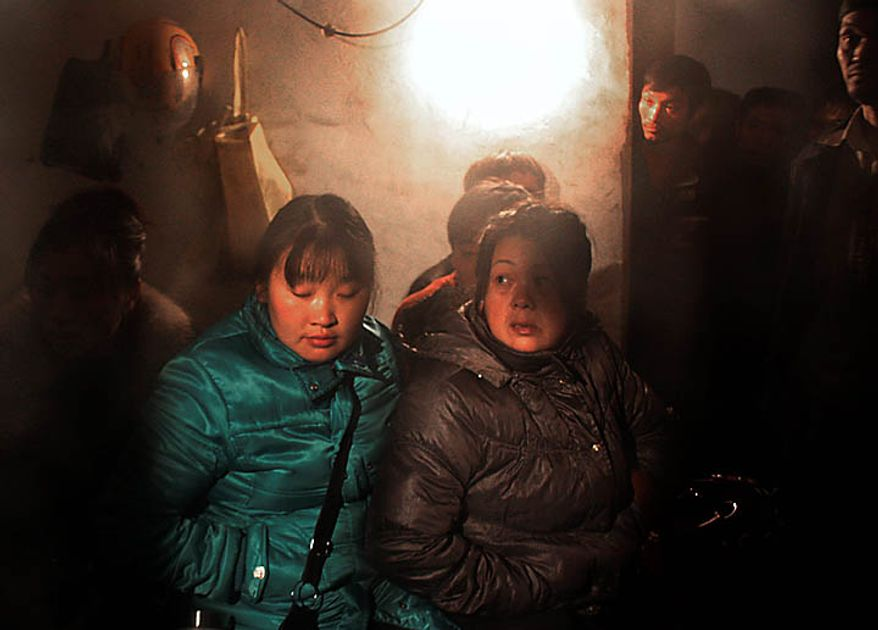 In this Sunday, Nov. 21, 2010 photo, relatives and workers waits for the news of the flooded Batian coal mine in Xiaohe town of Weiyuan county in southwest China's Sichuan province. Rescuers were racing Monday to reach 28 people trapped while doing safety work in coal mine in southern China, the latest accident in the world's deadliest mines.  (AP Photo/Color China Photo)