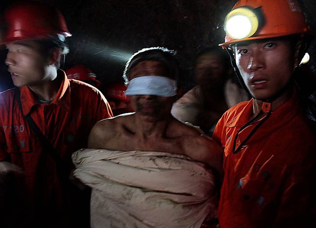 Rescuers escort a trapped miner wrapped in white quilt on their way out from the flooded Batian Coal Mine in Xiaohe town of Weiyuan county in southwest China's Sichuan province Monday, Nov. 22, 2010. Emergency crews drained th