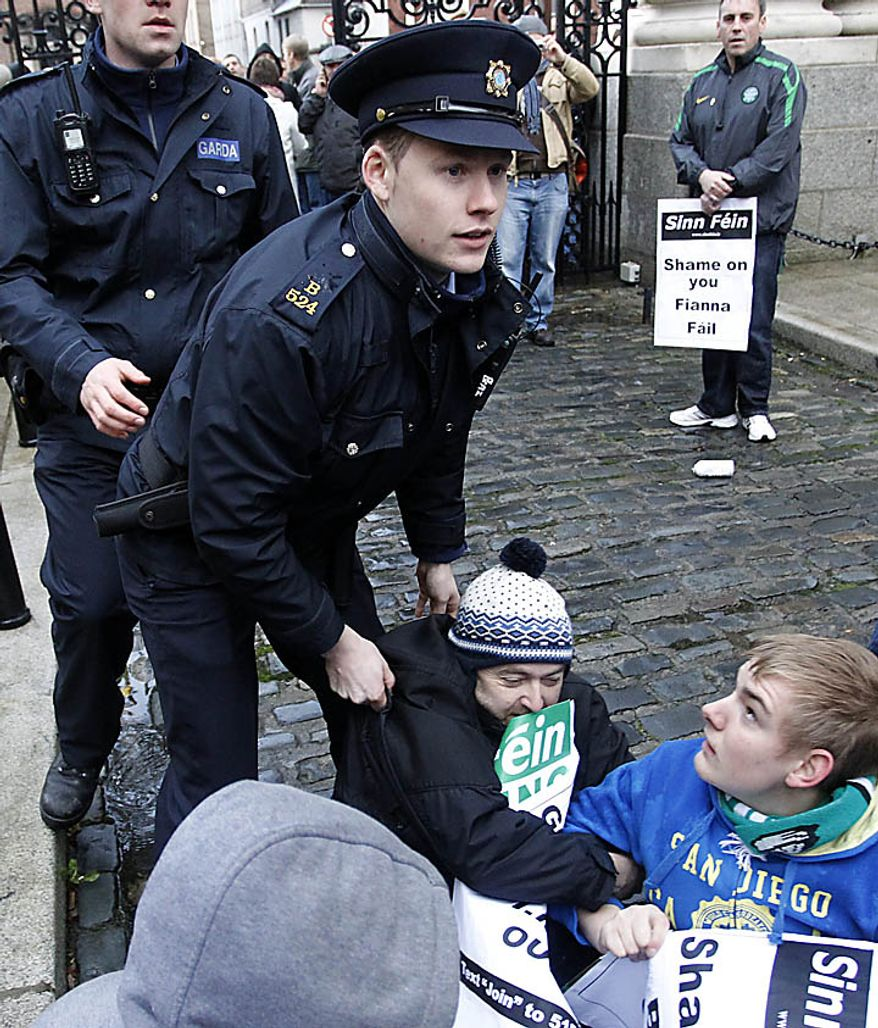 Irish police officers remove Sinn Fein protesters from inside the gates of government buildings in Dublin, Ireland, Monday, Nov. 22, 2010. The Sinn Fein protesters are calling for the Irish Prime Minister Brian Cowen to resign over the unfolding financial crisis.   (AP Photo/Peter Morrison)