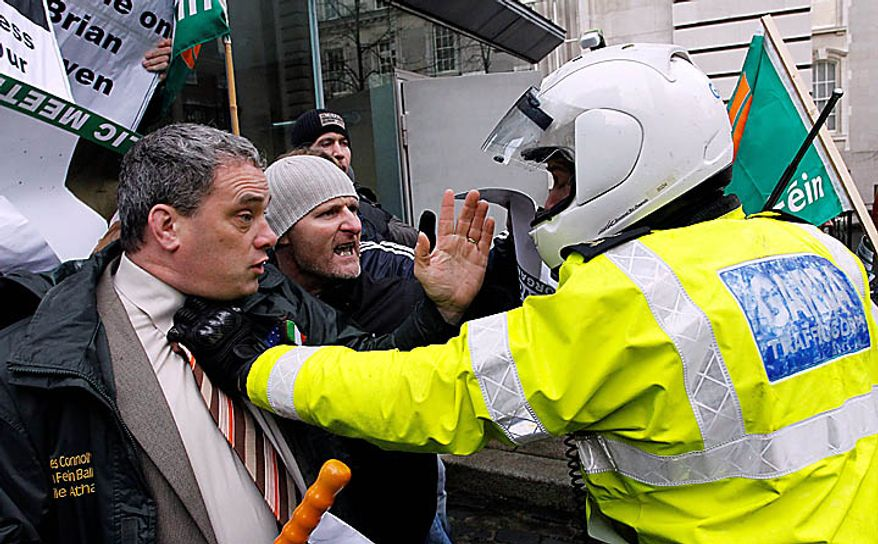 A motorcycle police officer holds back Sinn Fein protesters who broke through the gates at Government Buildings, Dublin, Ireland, Monday, Nov. 22, 2010.  The Sinn Fein protesters were calling for the Irish Prime Minister to resign, less than 24 hours after Irish cabinet ministers agreed to ask the International Monetary Fund and Europe for a multibillion bail-out.  (AP Photo/Peter Morrison)