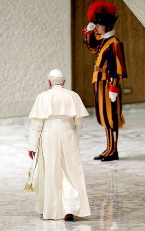 Pope Benedict XVI walks past a Vatican Swiss guard at the end of an audience with the newly-appointed cardinals and their relatives, in Hall Paul VI at the Vatican, Monday, Nov. 22, 2010. On Saturday the pope created 24 new cardinals. (AP Photo/Andrew Medichini)