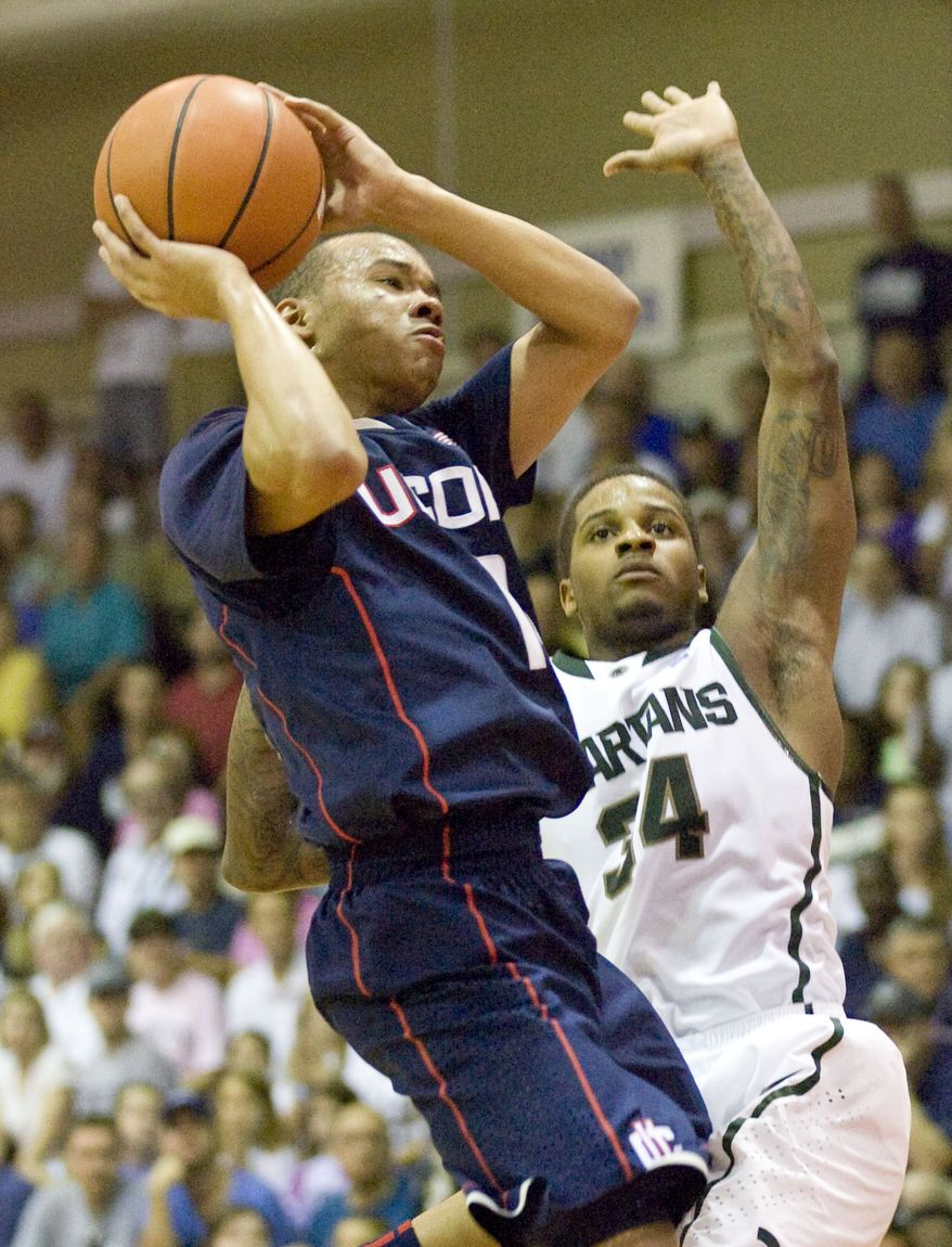 ASSOCIATED PRESS Connecticut guard Shabazz Napier, left, drives by Michigan State guard Korie Lucious, right, and puts up a shot in the first half of a NCAA college basketball game at the Maui Invitational in Lahaina, Hawaii Tuesday, Nov. 23, 2010.